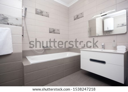 epmty minimalistic interior background, bathroom of modern apartment, mirror, bathtub and basin in light colors, nobody, with copy space, horizontal