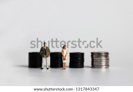 Equal labor equal pay concept. Miniature woman with a miniature man.