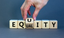 Equality or equity symbol. Businessman turns a cube and changs the word 'equality' to 'equity'. Beautiful grey background. Psychology, business and equality or equity concept. Copy space.