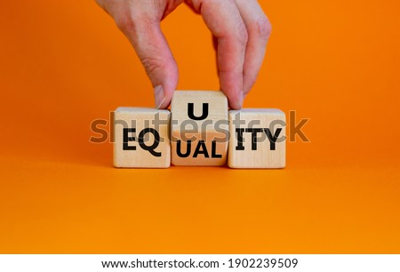 Equality or equity symbol. Businessman turns a cube and changs the word 'equality' to 'equity'. Beautiful orange background. Psychology, business and equality or equity concept. Copy space.