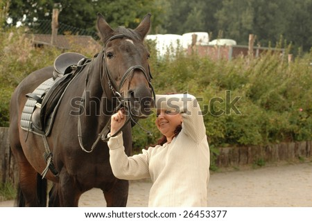 Equestrienne puts bridle on a horse.