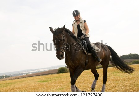 Equestrienne rides  across the field.