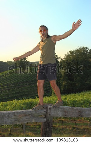 equilibrist walking on a wooden fence in Piedmont, Italy