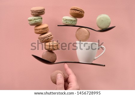 Equilibrium concept flat lay on coral color paper. Balancing cup of coffee and macarons on a finger