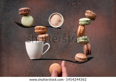 Equilibrium concept flat lay on dark grunge background. Balancing cup of coffee and macarons on a spoon