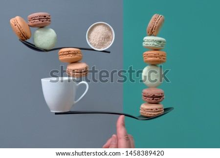 Equilibrium concept flat lay on gray and mint color paper background. Balancing cup of coffee and macarons on a spoon