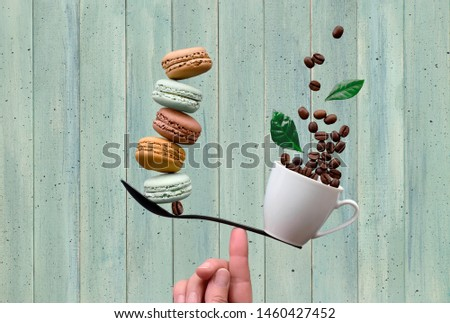 Equilibrium concept flat lay on mint colored wooden background. Balancing cup of coffee and macarons on a finger
