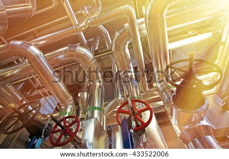 Equipment, cables and piping as found inside of a industrial power plant stock photo