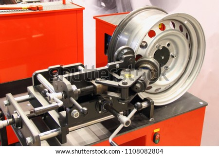 Equipment for car service and repair - tire machine for rolling and alignment of steel wheel rims close-up #1108082804