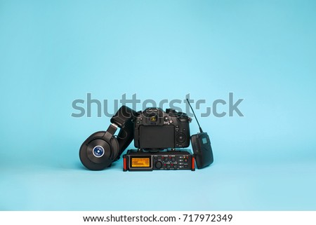 equipment for field video production, camera, boom mic, recorder and wireless system on blue background