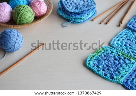Equipment for knitting and crochet hook, colorful rainbow cotton yarn, ball of threads, wool, knitted elements, napkin . Granny square. Handmade crocheting crafts. DIY concept. Copy space