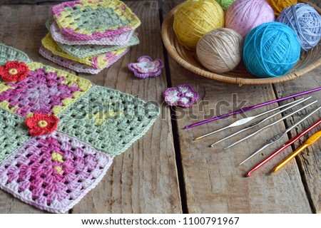 Equipment for knitting and crochet (hook, ?olorful rainbow cotton yarn, ball of threads, wool, knitted elements, napkin). Granny square. Handmade crocheting crafts. DIY concept. Copy space