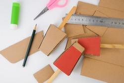 Equipment for making cardboard ice cream craft on white background: scissors, pencil, glue, rulers, old cardboard.