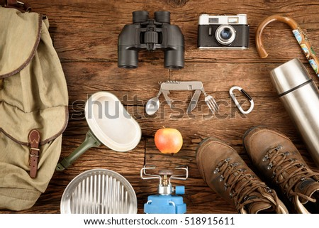 Equipment for mountaineering and hiking on wooden background