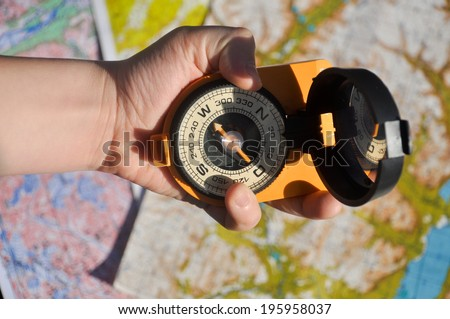 Equipment for orientation on terrain. The compass in his hand on the topographic maps.