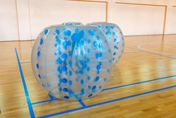 Equipment for team building sport game named bumper ball or bubble ball. Zorbsoccer. Blue bumper boll bubble balloons in the sports center. Selective focus