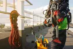 Equipment of industrial mountaineering worker on roof of building during industrial high-rise work. Climbing equipments before starting job. Rope laborer access. Concept of urban works. Copy space