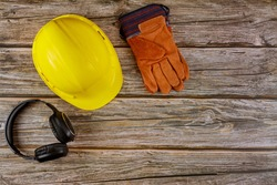 Equipment safety standard construction safety earmuffs leather safety helmet protective gloves on wooden table top view