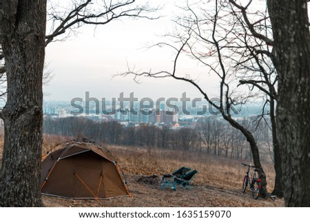 Equipped camp in the forest. Camping tent and portable chairs and table. Cold autumn day. outdoor. nobody. bonfire and bicycle, city on distance. run away from the bustling city and the bustle