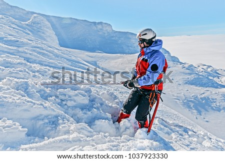 Equipped climber ascent by snowy slope with climbing rope on the top of peak in snowy alpine mountains. Life guard professional man on the work in high mountains. Action in hard conditions scene. #1037923330