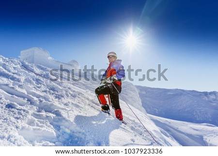 Equipped climber ascent by snowy slope with climbing rope on the top of peak in snowy alpine mountains. Life guard professional man on the work in high mountains. Action in hard conditions scene. #1037923336