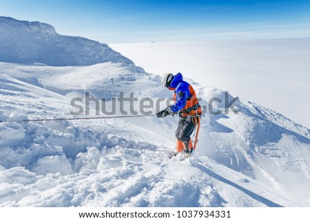 Equipped climber ascent by snowy slope with climbing rope on the top of peak in snowy alpine mountains. Life guard professional man on the work in high mountains. Action in hard conditions scene. #1037934331