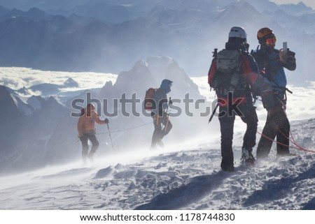 Equipped climber ascent by snowy slope with climbing rope on the top of peak in snowy alpine mountains. Life guard professional man on the work in high mountains. Action in hard conditions scene. #1178744830