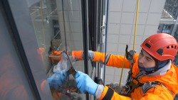 equipped window washer in a helmet and orange jumpsuit washes glass with a screed at high altitude of a multi-story apartment building, slow motion