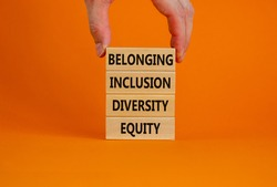 Equity, diversity, inclusion and belonging symbol. Wooden blocks with words equity, diversity, inclusion, belonging on beautiful orange background. Diversity, equity, inclusion and belonging concept.