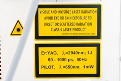 ER:Yag laser machine safety label, on side of device, in yellow and black, with warnings and specifications of laser wavelengths and dangers if not used properly. Class 4 laser product.