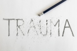 Erasing trauma. Trauma written on white paper with a pencil, partially erased with an eraser. Symbolic for overcoming trauma or treating trauma.