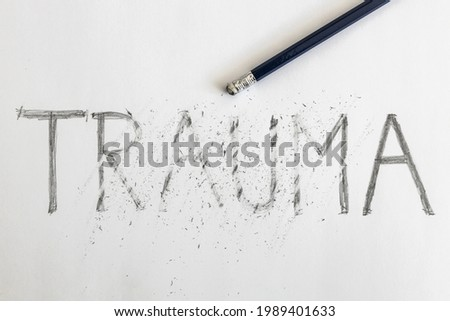 Erasing trauma. Trauma written on white paper with a pencil, partially erased with an eraser. Symbolic for overcoming trauma or treating trauma.   Foto d'archivio ©