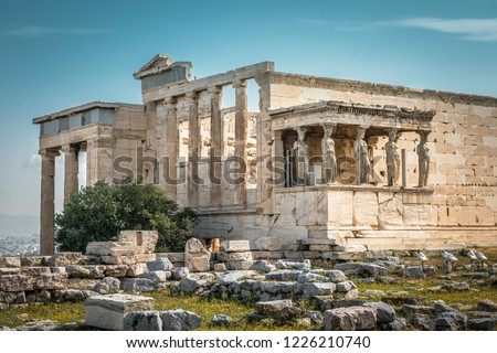 Erechtheion temple with Caryatid Porch on the Acropolis, Athens, Greece. Famous old Acropolis hill is top landmark of Athens. Ancient Greek ruins in Athens center. Remains of antique Athens in summer.