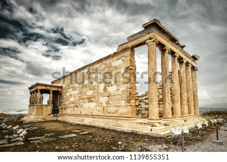 Erechtheion temple with Caryatid Porch on the Acropolis in Athens, Greece. Famous Acropolis hill is the main landmark of Athens. Ancient Greek ruins at the top of Acropolis under dramatic sky.