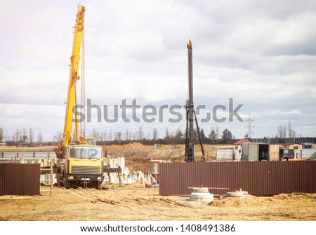 Erection of a foundation for a multi-storey residential building, a truck crane lifts roadhead piles, piling machinery, diesel hammer, special equipment