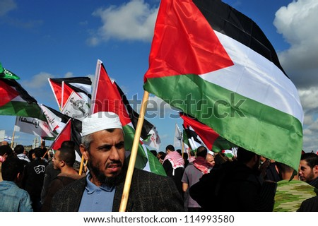 EREZ CROSSING-DECEMBER 31:Palestinian Arabs carry Palestinian flags during a protest on the Gaza-Israel border on Dec 31 2009.The entire  Palestinian population in Gaza Strip is 1.6 million people