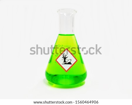 Erlenmeyer flask with Green liquid and chemical hazard warning symbols labels (hazardous to the environment sign) on white background.