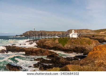 Ermida de Nosa Señora do Porto and the faro de Punta Frouxeira in background in Galicia, Spain.  Zdjęcia stock ©