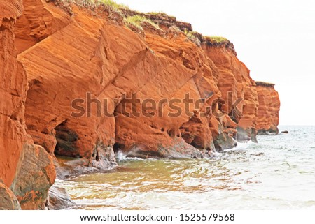 Eroded red sandstone cliffs are typical of landscapes and seascapes in Canada's Madeleine Islands.