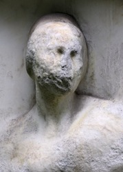 Eroded stone sculpture memorial grave at the cemetery.