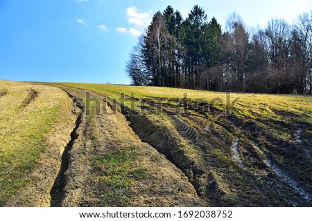 Erosion of soil and grass in landscape with erosive grooves on path through grass field on a hill, environmental destruction. Photo stock ©