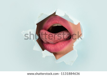 Erotic tongue in mouth. Oral sex. Intimate care and tenderness. Young woman plays with tounge in paper hole. Close up female open mouth and tounge that is seen through a hole in light blue background