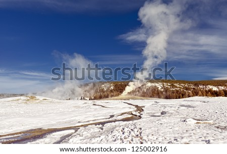 Eruption of Old Faithful Geyser at Yellowstone National Park in the Winter