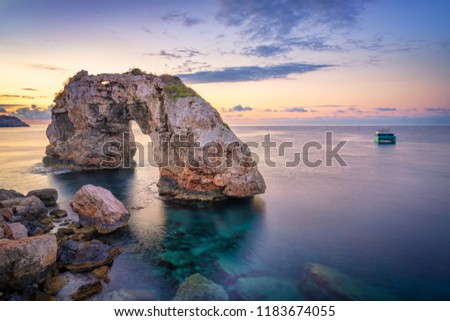 Es Pontas in Mallorca with boat anchored nearby in the Mediterranean sea.  Sunrise with yacht and rock arch near Santanyi Majorca Foto stock ©