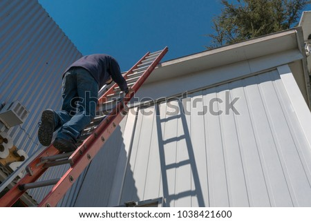 Escalating risks of a worker by ladder to work on the roof of a house. #1038421600