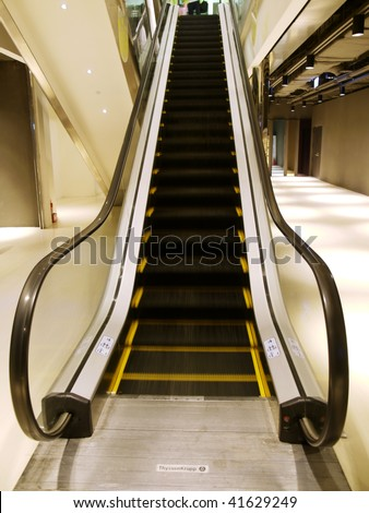 Escalator in department store - stock photo