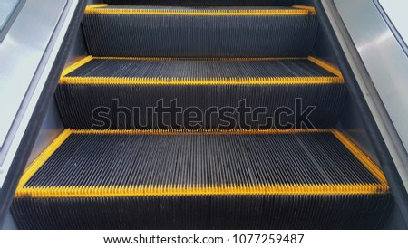Escalator in metro. Moving up staircase,Close up to Moving electric.yellow bands metal line steel. yellow gray steel line.