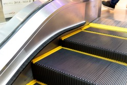 Escalator in underground. Moving up staircase. escalator. electric escalator.. yellow bands. metal line steel. yellow gray steel line