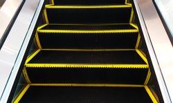 Escalator. Moving up staircase. escalator. electric escalator.Close up to escalators.Close up floor platform. yellow bands. metal line steel. yellow gray steel line. Escalator Background