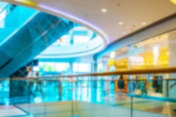 Escalator people blurred background. Interior of retail centre store in soft focus. People shopping in modern commercial mall center. Sale, consumerism and people concept.